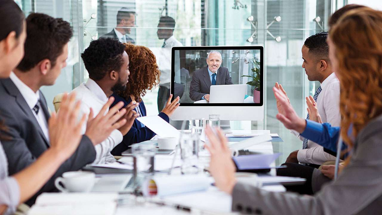 Seven People Sitting at Table in Video Conference